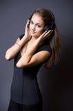 Brunette joven magnífico que escucha la música. Imagenes de archivo
