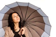 Brunette joven que controla el cielo para saber si hay lluvia Imágenes de archivo libres de regalías
