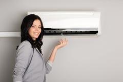 Brunette joven que muestra el acondicionador de aire Imágenes de archivo libres de regalías
