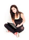 Brunette joven que usa la computadora portátil. Foto de archivo