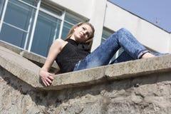 Brunette-Jugendliche, die auf der Wand sitzt Stockbild