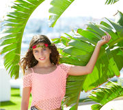 Brunette kid girl at banana tree leaves in bright day Royalty Free Stock Images