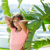 Brunette kid girl at banana tree leaves in bright day Royalty Free Stock Photo