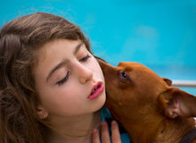 Brunette kid girl and dog pet whispering ear Stock Images