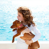 Brunette kid girl with dog on the sea. View from a boat Stock Photography