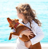 Brunette kid girl with dog on the sea Stock Photography