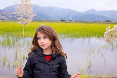 Brunette kid girl outdoor holding spike in wetlands lake. Meadow Stock Images