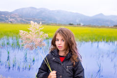 Brunette kid girl outdoor holding spike in wetlands lake Royalty Free Stock Image
