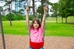 Brunette kid girl playing with swing on city park Stock Photography