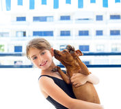Brunette kid girl in swimsuit playing with dog Royalty Free Stock Photography