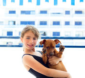 Brunette kid girl in swimsuit playing with dog Stock Photography