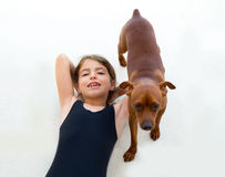 Brunette kid girl in swimsuit playing with dog Royalty Free Stock Image