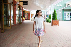 Brunette kid girl walking around shopping center Royalty Free Stock Photography