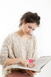 Brunette in knitted pullover sitting and reading a book. With white background Stock Photography
