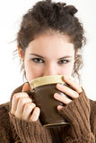 Brunette in knitted pullver drinking from a mug. With white background Stock Photos