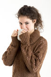 Brunette in knitted pullver drinking from a mug. With white background Stock Photography