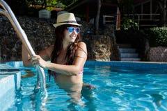 Brunette on ladder of pool Royalty Free Stock Image