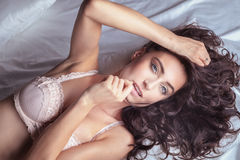 Brunette lady in bed Royalty Free Stock Images
