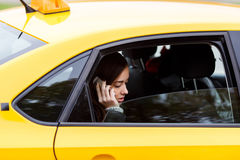 Brunette lady in classic yellow cab talking on mobile phone Stock Photography