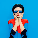 Brunette lady with fashion haircut and sunglasses on a blue back Stock Photography