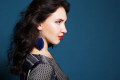Brunette lady with feather earring. Brunette girl with feather earring royalty free stock images