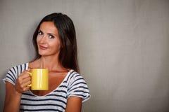 Brunette lady holding mug while looking at camera Stock Photos