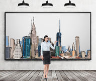 A brunette lady is pointing out the picture of New York City on the wall. Wooden floor, concrete wall and three black ceiling ligh Royalty Free Stock Photo