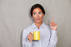 Brunette lady pointing up and holding hot tea. Brunette lady pointing up while holding hot tea with open mouth and looking away on grey texture background - copy Royalty Free Stock Photography