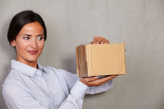 Brunette lady smiling while opening package Royalty Free Stock Photography