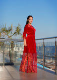 A brunette lady standing on a balcony on a blue sky background. A fashionable woman in a long red dress. A female on a stock image