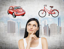 A brunette lady is trying to chose the most suitable way for travelling or commuting in the city. Sketches of a car, a bicycle and Royalty Free Stock Photography