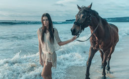 Brunette lady walking with a horse. Brunette lady walking with a majestic horse stock photos