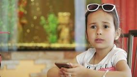 Brunette Latina Kind des kleinen Mädchens, das im Café, spielend auf Smartphone im Spiel sitzt, empört, unglücklich stock video footage