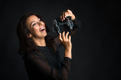 Brunette laughing woman holding  vintage camera Royalty Free Stock Photography