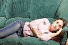 Brunette laying down on green sofa Stock Photo