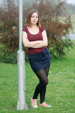 Brunette leaning against street pole Stock Photography