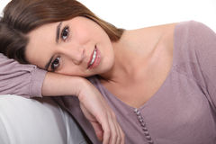 Brunette leaning on sofa Royalty Free Stock Photos