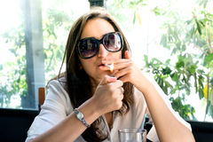 Brunette lighting a cigarette, having a smoke Royalty Free Stock Photos