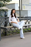 Brunette listening music at bus-stop Stock Image