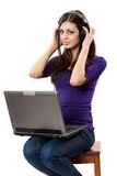 Brunette listening music from laptop. Young brunette lady sitting on a chair with headphones connected to laptop Royalty Free Stock Photo