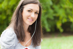 Brunette listening to music outdoors Royalty Free Stock Photography