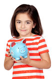 Brunette little girl with a blue moneybox. Isolated on a over white background Royalty Free Stock Photo