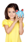 Brunette little girl with a blue moneybox Royalty Free Stock Images