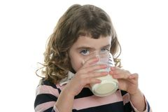 Brunette little girl drinking glass of milk Royalty Free Stock Photography