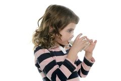 Brunette little girl drinking glass of milk Stock Photo