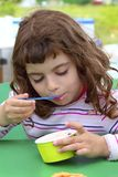 Brunette little girl eating ice cream Royalty Free Stock Photography