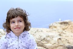 Brunette little girl funny gesture near sea Stock Photo