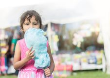 Brunette little girl at the town fair eating cotton candy. Black eyes, with pink dress, with unfocused background, little girl having fun at the fair royalty free stock images