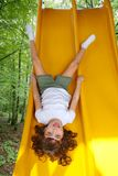 Brunette little girl upside down playground slide Stock Photos