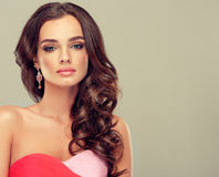 Brunette with long curled hair. Royalty Free Stock Photos